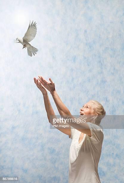 mature woman releasing dove - loslassen aktivitäten und sport stock-fotos und bilder