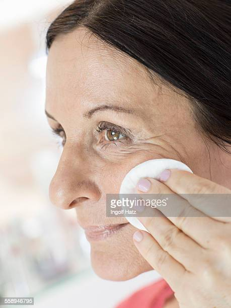 Mature woman removing make up from face with cotton pad