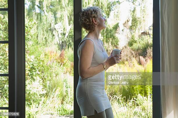Mature woman resting against door