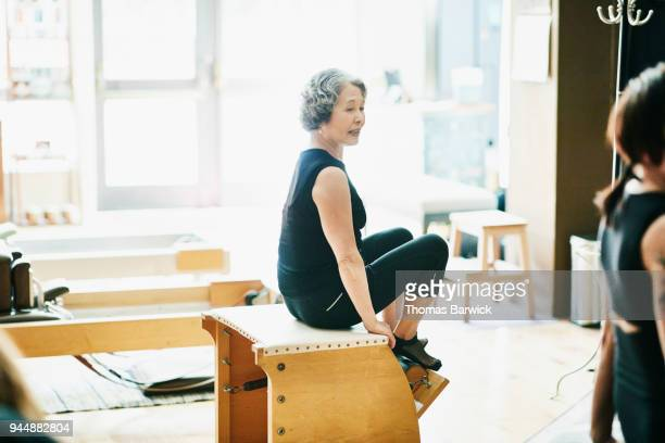 Mature woman resting between exercises during class in pilates studio