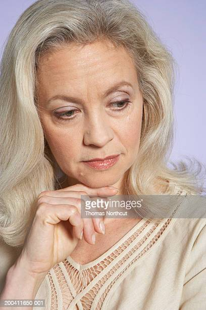 mature woman resting chin on hand, looking down - down blouse stock pictures, royalty-free photos & images