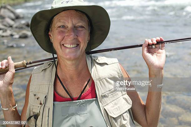 Mature woman resting fishing pole on shoulders beside river, portrait