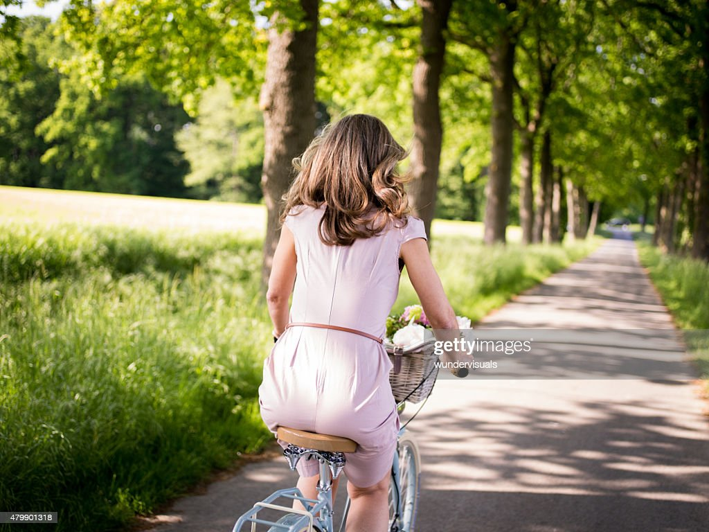 mature woman riding a bicycle through a summer park stock photo