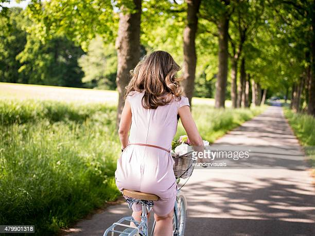 Mature woman riding a bicycle through a summer park