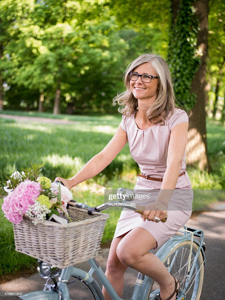 mature woman riding a vintage bicycle in a park stock photo | getty