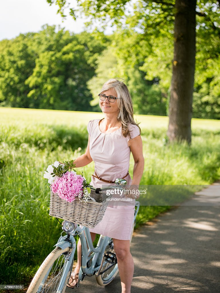 Mature Woman Riding A Vintage Bike Through A Park High-Res Stock Photo - Getty Images-4496