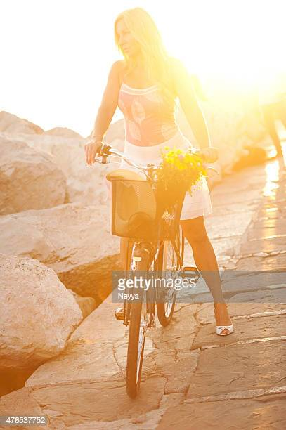Mature woman riding bicycle against sun