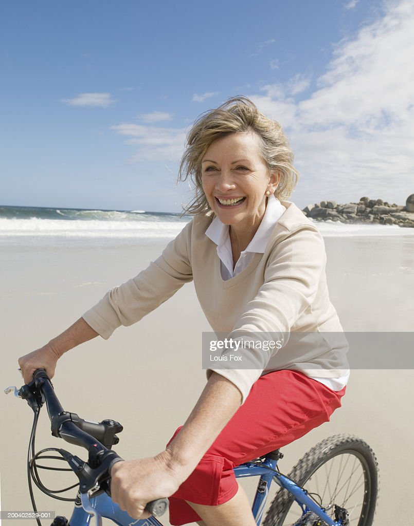 mature woman riding bicycle on beach smiling portrait stock photo