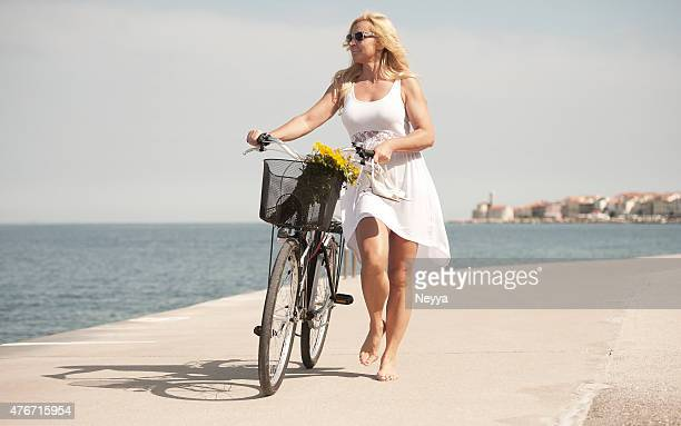 mature woman riding bicycle - minirok stockfoto's en -beelden