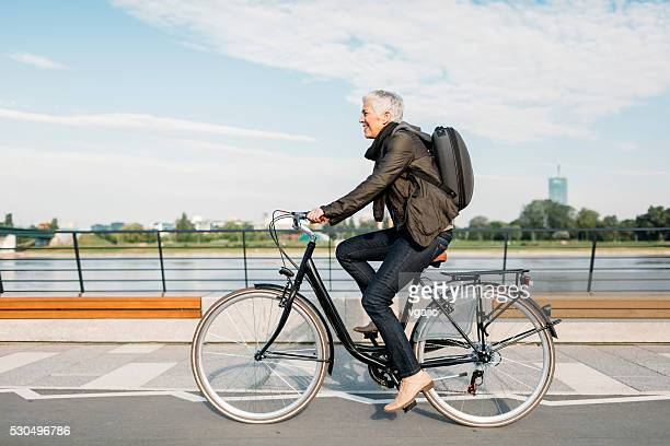 mature woman riding bicycle. - belgrade serbia stock pictures, royalty-free photos & images