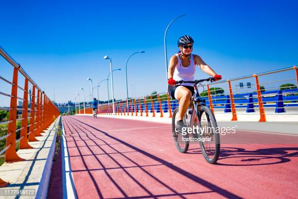 mature woman riding bycicle in a sunny day - bicycle lane stock pictures, royalty-free photos & images