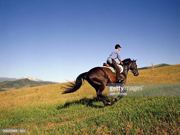 Mature woman riding  horse, side view