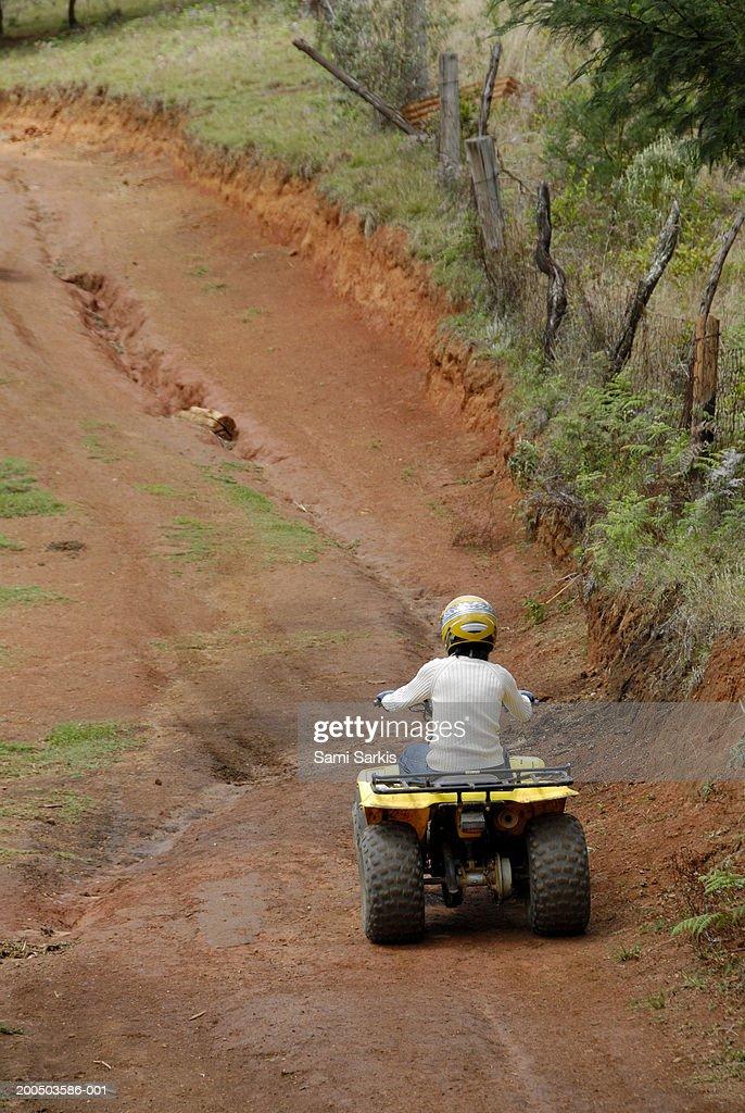 Mature woman riding quadbike on dirt road, rear view : Stock Photo