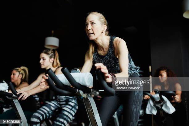 Mature woman riding stationary bike during class in cycling studio