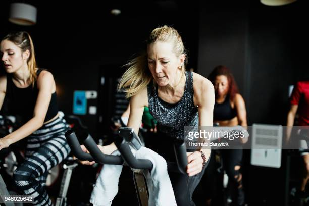 Mature woman riding stationary bike during fitness class in cycling studio