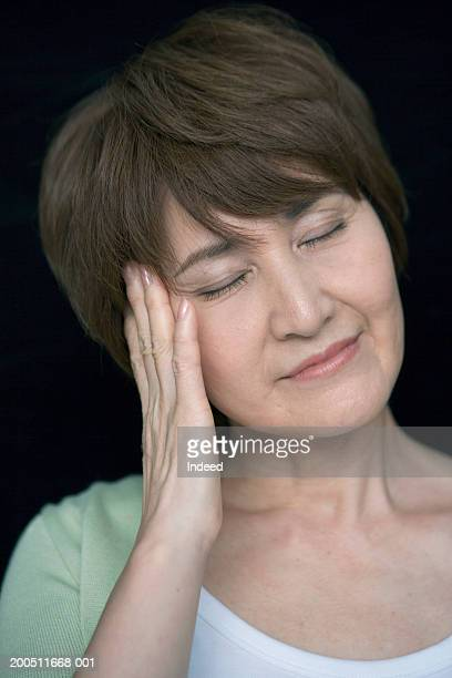 Mature woman rubbing temple, eyes closed, close-up, portrait