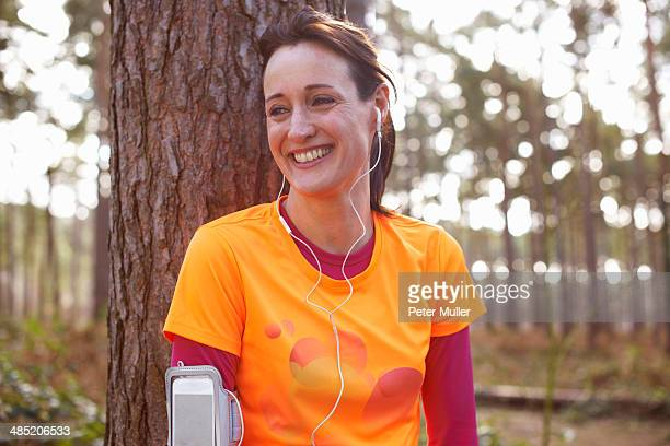 Mature woman runner with earphones taking a break in a forest