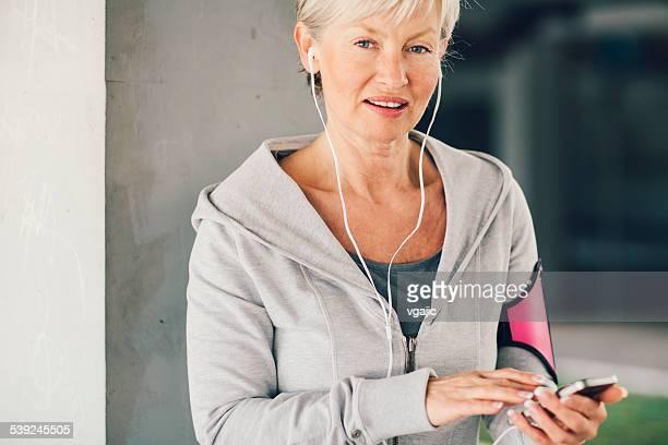 Mature Woman Running and listening music.