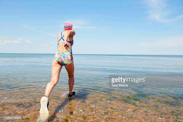 mature woman running into sea - sea stock pictures, royalty-free photos & images