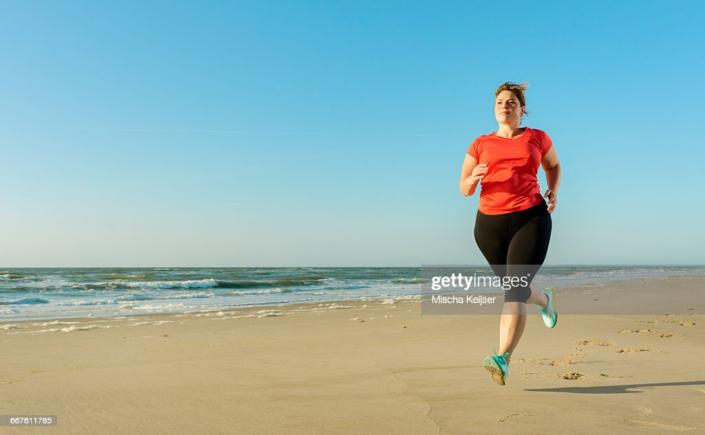 Mature woman running on a beach at sunset : Stock Photo