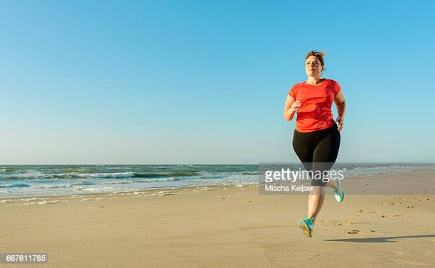 mature woman running on a beach at sunset - dikke vrouw stockfoto's en -beelden