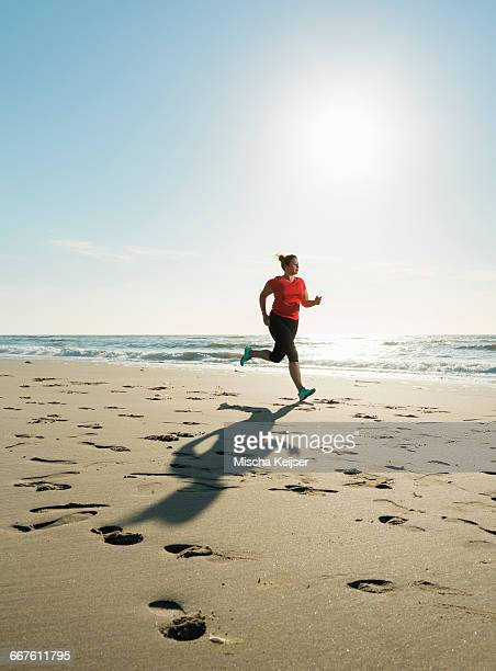 mature woman running on a beach at sunset - fat lady in leggings stock photos and pictures