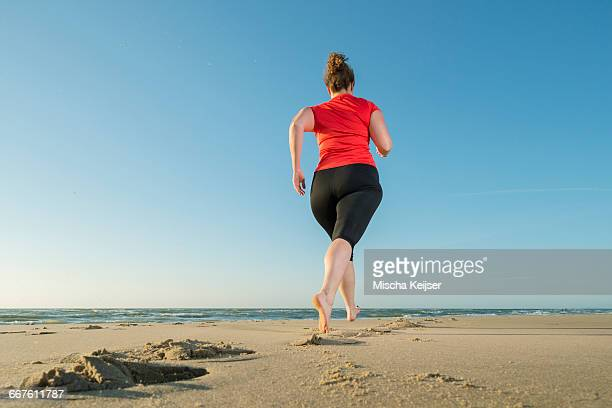 mature woman running on a beach at sunset, rear view - fat woman at beach stock photos and pictures