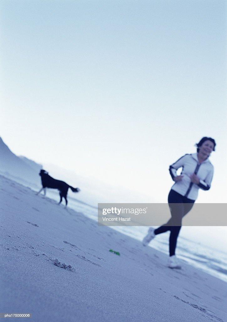 Mature woman running on beach : Stockfoto