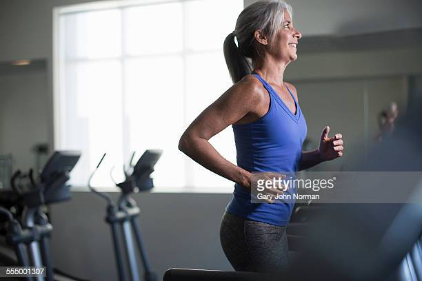 Mature woman running on gym treadmill