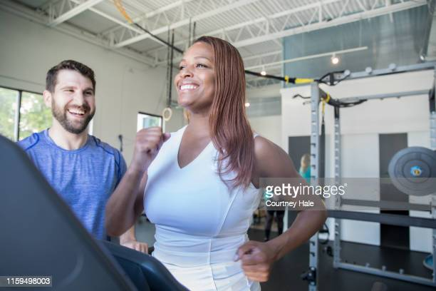 mature woman running on treadmill while being coached by personal trainer - fitness instructor stock pictures, royalty-free photos & images
