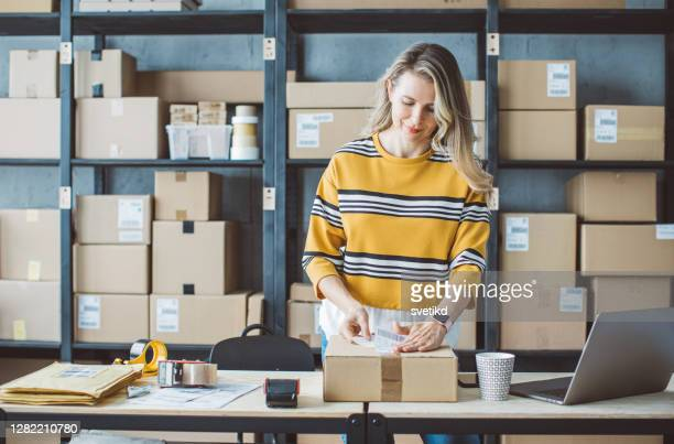 mature woman running online store - cardboard box stock pictures, royalty-free photos & images