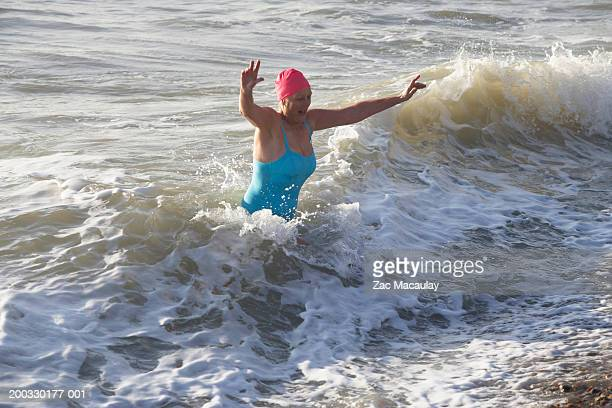 Mature woman running out of wave, elevated view