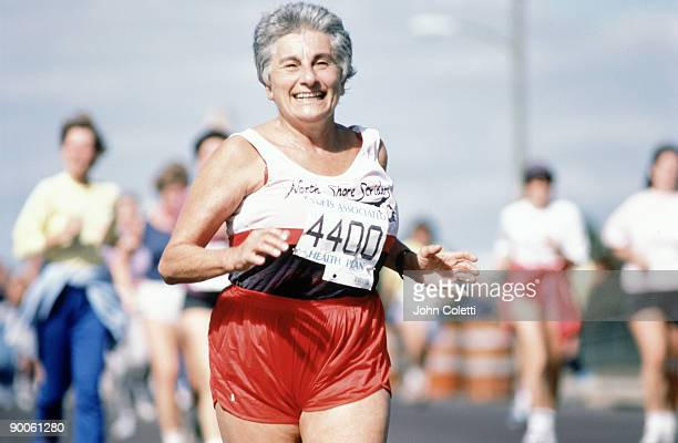 a mature woman runs in a marathon - marathon stock pictures, royalty-free photos & images