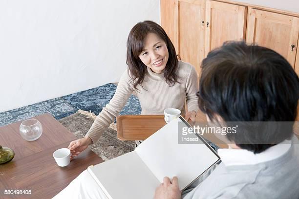 Mature woman serving coffee to senior man