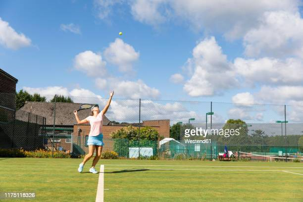 mature woman serving during a tennis match on grass court - tennis stock pictures, royalty-free photos & images