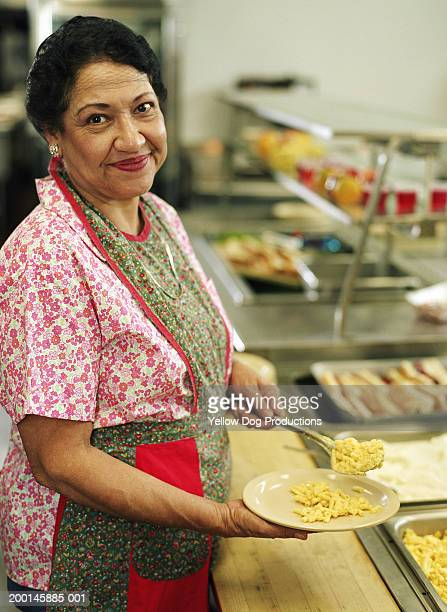 Mature woman serving food in cafeteria, portrait
