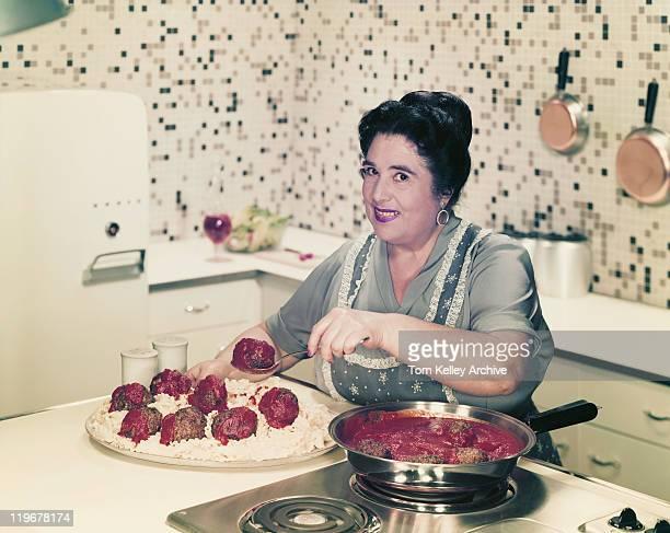 mature woman serving meatballs on noodles, smiling, portrait - 1957 stock pictures, royalty-free photos & images