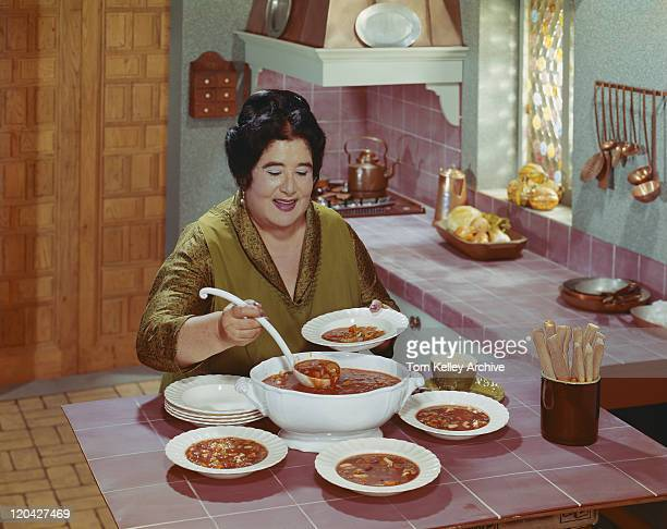 Mature woman serving soup in bowl, smiling