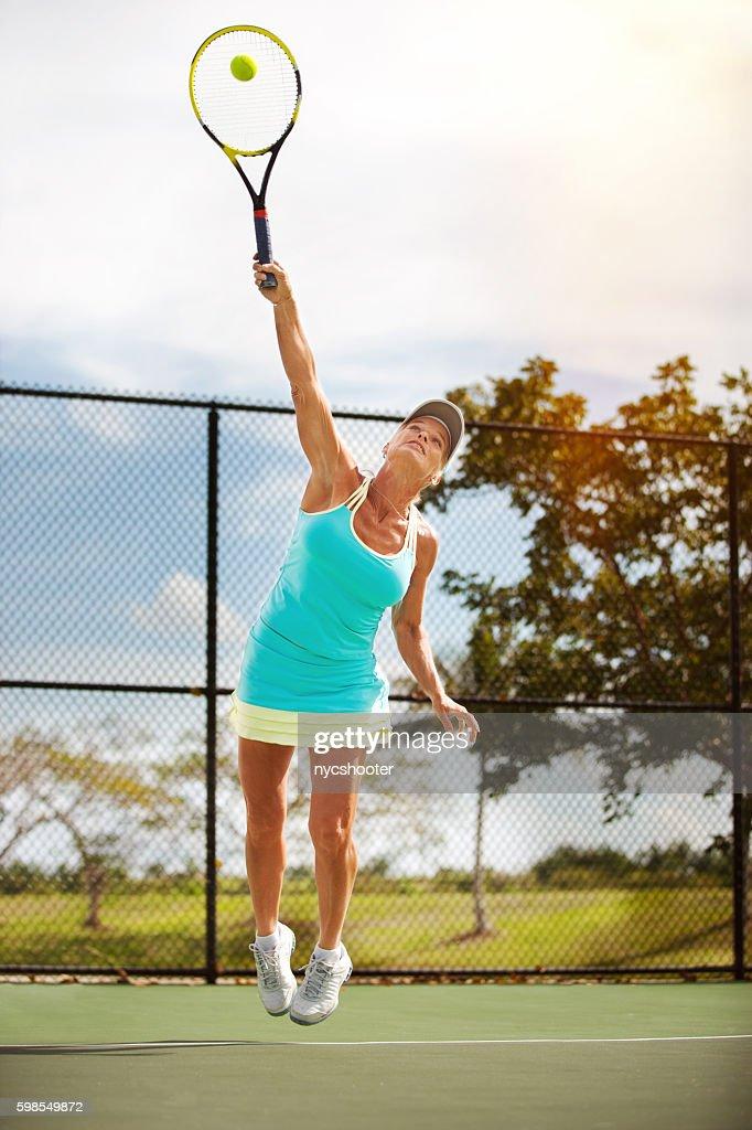 Donna matura che servono Pallina da tennis : Foto stock