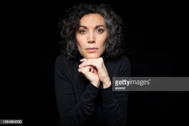 mature woman shivering with cold on black background - retrato formal imagens e fotografias de stock
