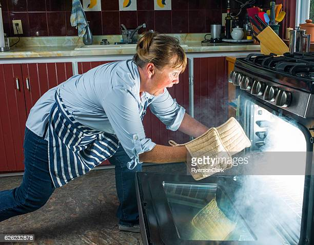 Mature woman shocked at oven fire in kitchen.