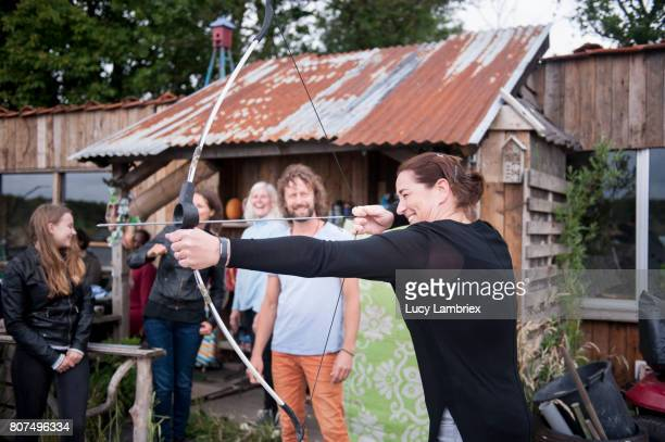 Mature woman shooting bow and arrow