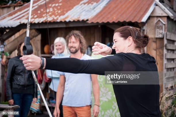 Mature woman shooting bow and arrow