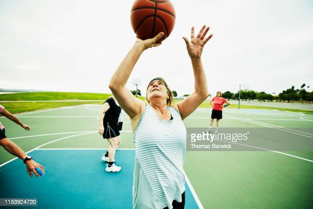 mature woman shooting layup during basketball game on outdoor court - shooting baskets stock pictures, royalty-free photos & images