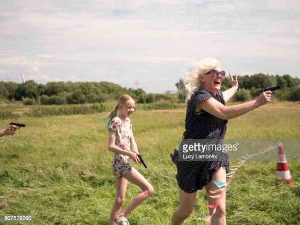 Mature woman shooting with her water gun in a water fight