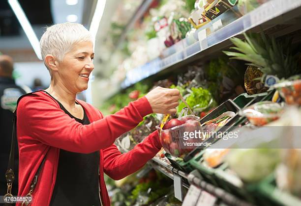 mature woman shopping at market - produce aisle stock photos and pictures