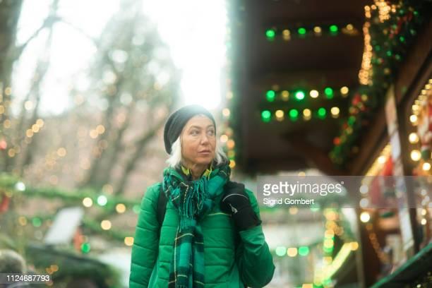 mature woman shopping at weihnachtsmarkt, freiburg, baden-wurttemberg, germany - sigrid gombert stock-fotos und bilder