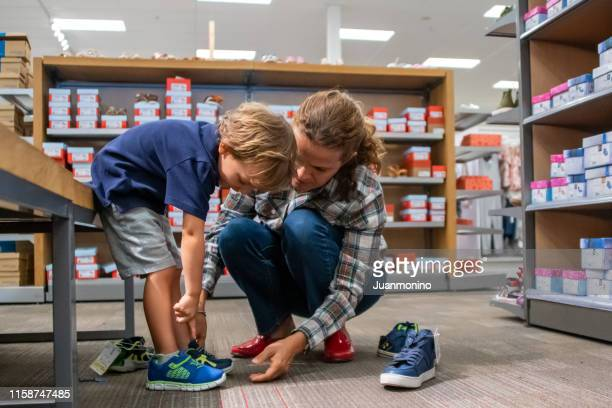 mature woman shopping for shoes for her son - footwear stock pictures, royalty-free photos & images