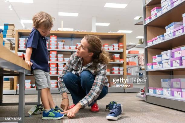 mature woman shopping for shoes for her son - shoe store stock pictures, royalty-free photos & images