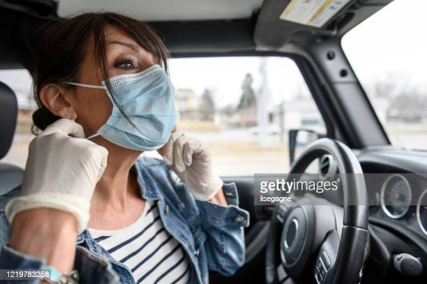 mature woman shopping grocery, removing mask in the car - driving mask stock pictures, royalty-free photos & images